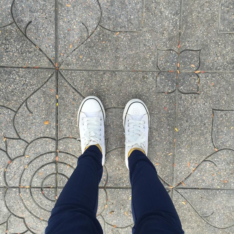 Gumshoes on urban grunge background. Conceptual image of legs. royalty free stock image