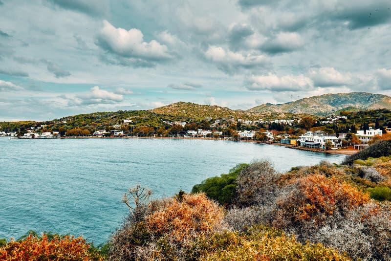 Gumusluk海湾和村庄在博德鲁姆,Mugla,土耳其喜怒无常的看法在一个多云冬日 美丽的风平浪静、草甸和天空 免版税图库摄影