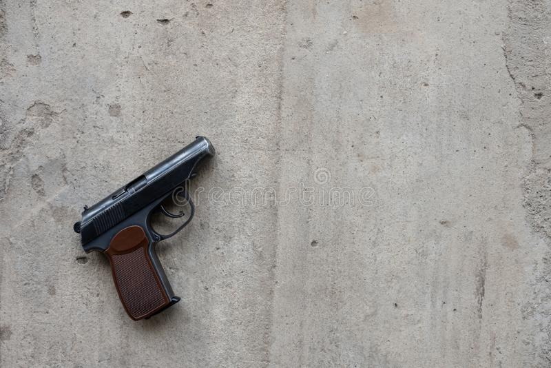 Metal gun on a gray concrete background. top view, flat lay, copy space stock photography