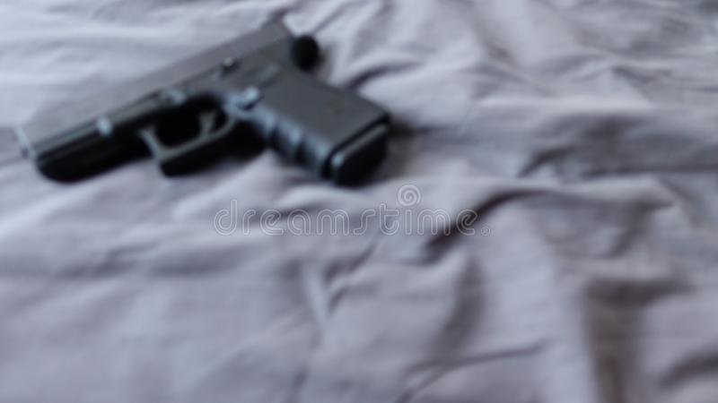 Gun on bed, ready to protect from another bad people, b&w crime scene conceptual. stock photography