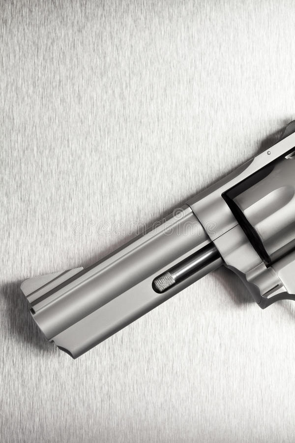 Gun on brushed metal background stock photography