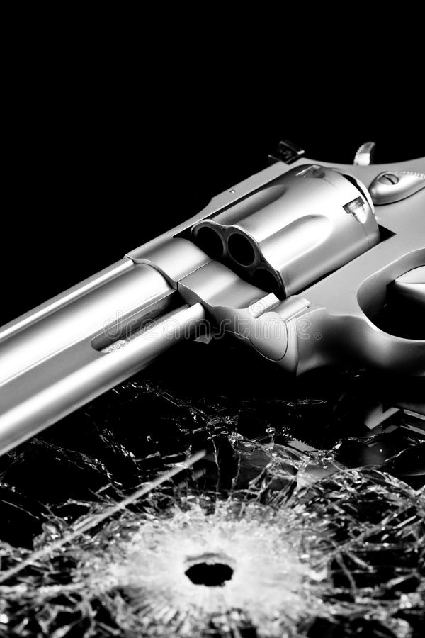 Gun with bullet hole in glass stock image