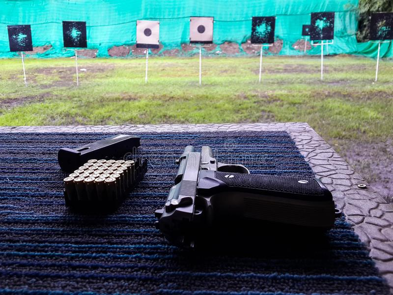 Gun with bullets pack and magazine on table against shooting target in shooting sport club stock photography