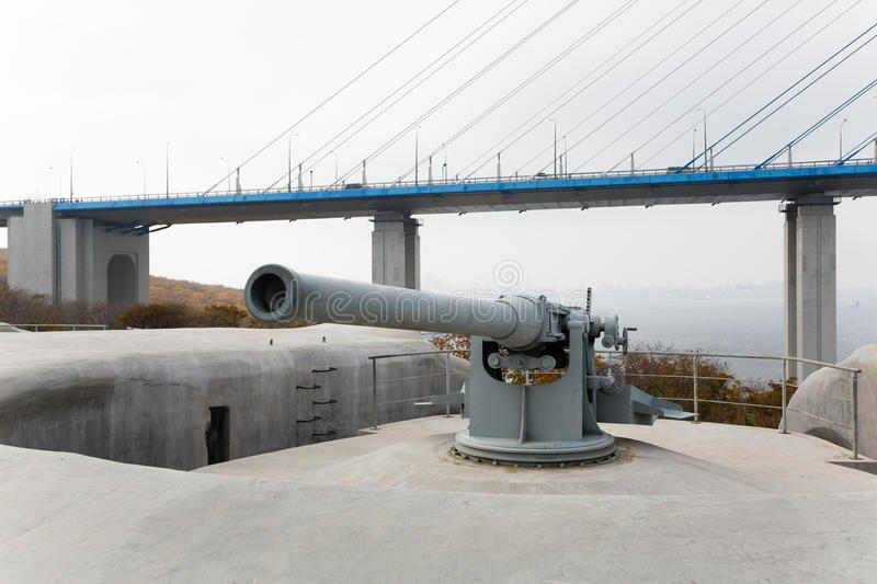 Gun of coastal batterie in Vladivostok fortress. And Cable-stayed bridge. Island of Russian, Vladivostok, Russia royalty free stock images