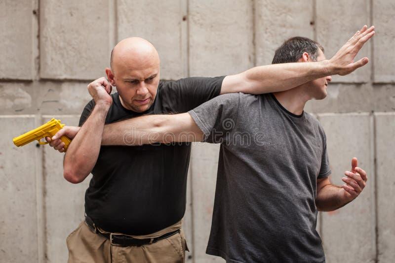 Gun Disarm. Self defense techniques against a gun point. Kapap instructor demonstrates self defense techniques against a gun point. Gun Disarm royalty free stock photos