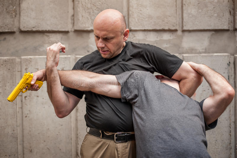 Gun Disarm. Self defense techniques against a gun point. Kapap instructor demonstrates self defense techniques against a gun point. Gun Disarm stock images