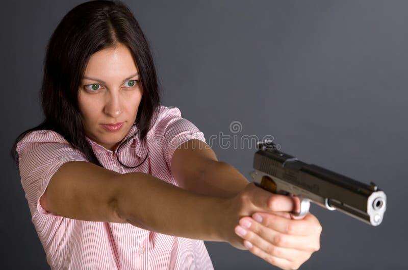 Gun and girl. Pretty caucasian girl with gun aiming to somebody over gray stock photos
