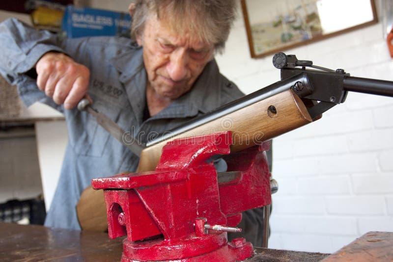 gun hans man som reparerar seminariet arkivbild