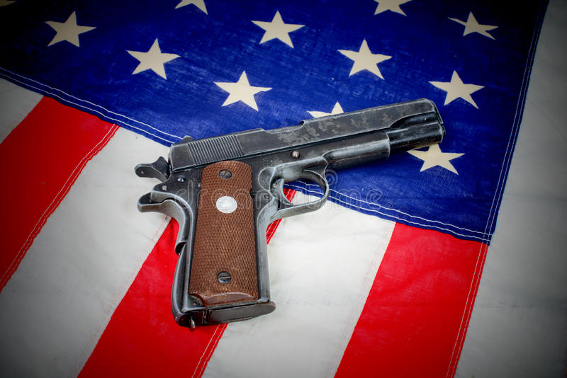 Gun laid on the American flag. Close-up stock photography