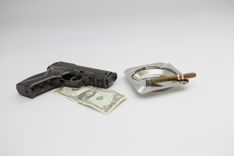 Gun money and cigar separated at the white background royalty free stock photos