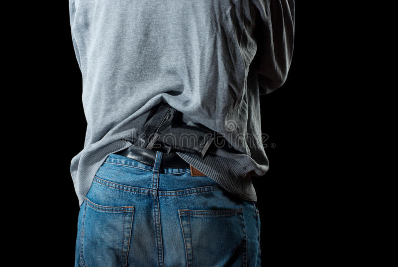 Gun in Pants. Man`s back with gun tucked in pants. Isolated on white background royalty free stock photos