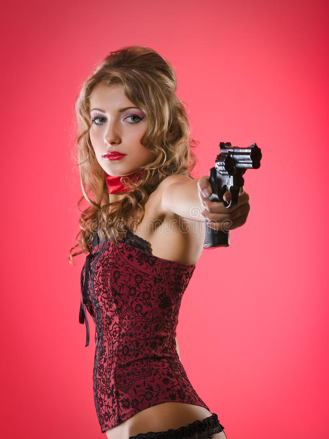 At gun point. Beauty girl aims with revolver stock photos