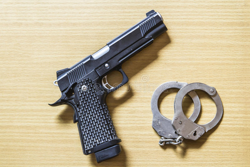 Gun and shackle on wood stock image