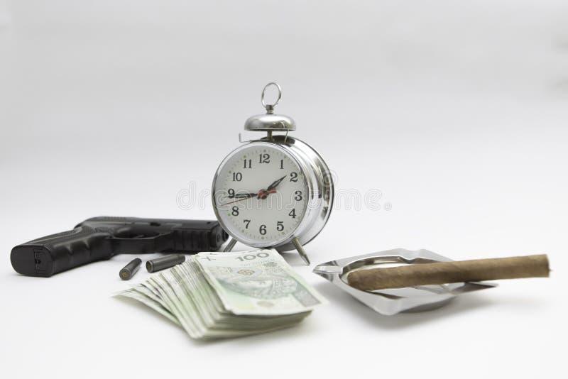 Gun money cigar clock at the white background. Gun with shells, money, cigar, clock and ashtray separated at the white background stock image