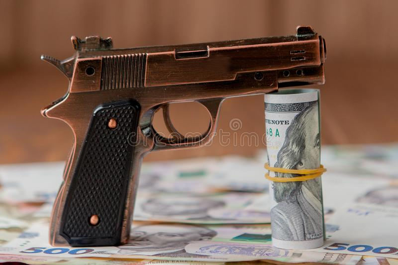Gun and Stack of Money lying on the hryvnia on a wooden table. Drug use, crime, addiction and substance abuse concept on wooden stock photo