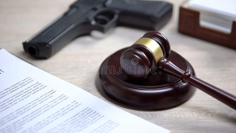 Gun on table, gavel lying on sound block, illegal use weapon, court hearing. Stock photo royalty free stock photo