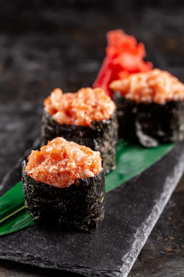 Gunkan Maki Sushi mit mit Lachsen auf einem Bambusblatt und auf einem schwarzen Steinschiefer Ein horisontal Bambuszaunhintergrun lizenzfreies stockfoto