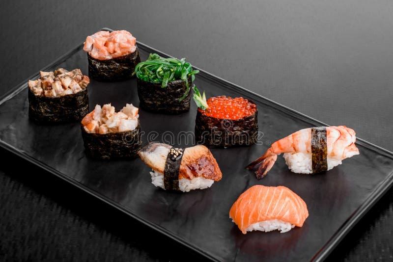 Gunkan och sushiuppsättning med laxen, ålen, räka, chukka och höna på en svart platta på en mörk bakgrund close upp royaltyfri foto