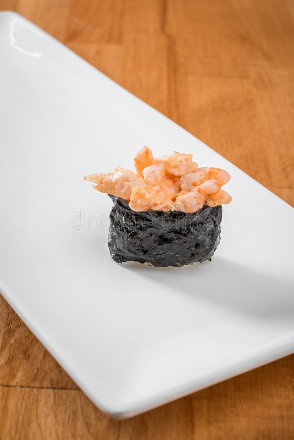 Gunkan with shrimp on a white plate on a warm background. Japanese traditional sushi royalty free stock images