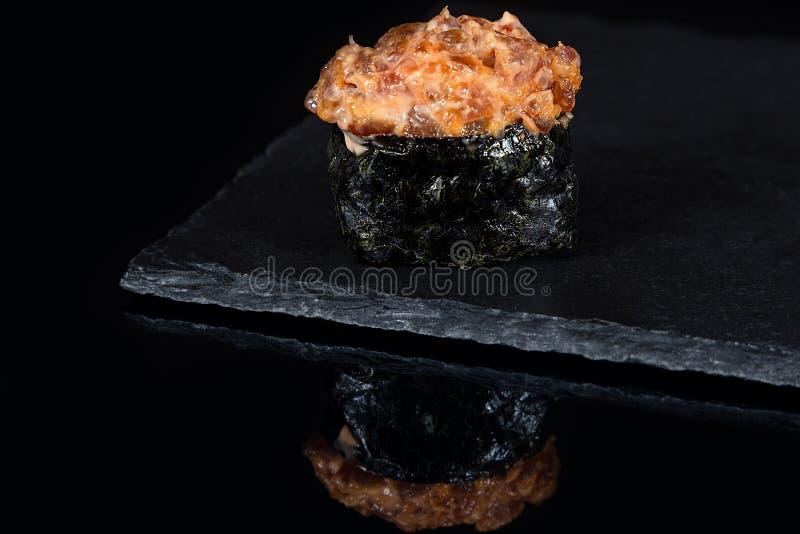 Gunkan-Sushi mit würzigem Thunfisch auf schwarzem Schreibtisch lizenzfreie stockfotografie