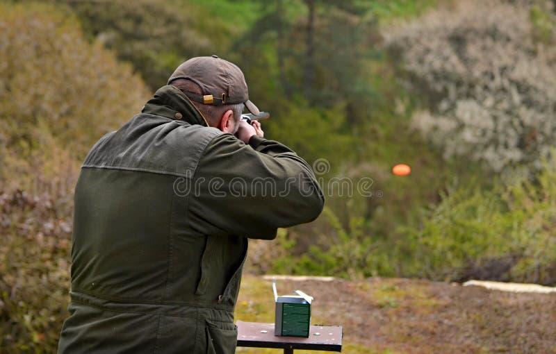 Gunman shooting the asphalt pigeon royalty free stock photos