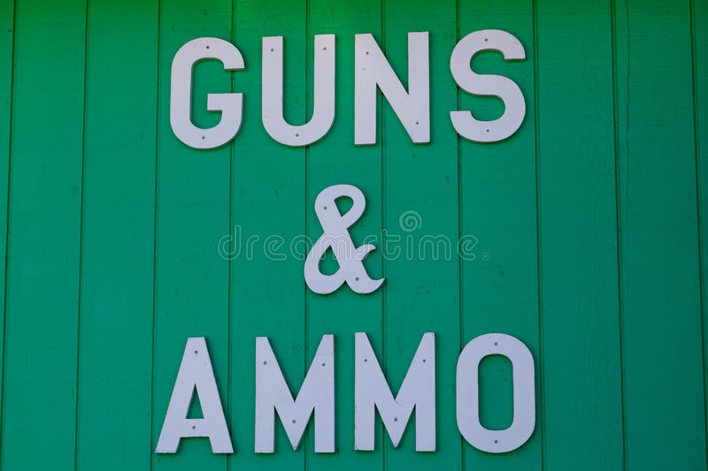 Guns and Ammo Sign. A white cutout letter sign nailed to a wall of a gun shop advertising guns and ammo for sale stock images