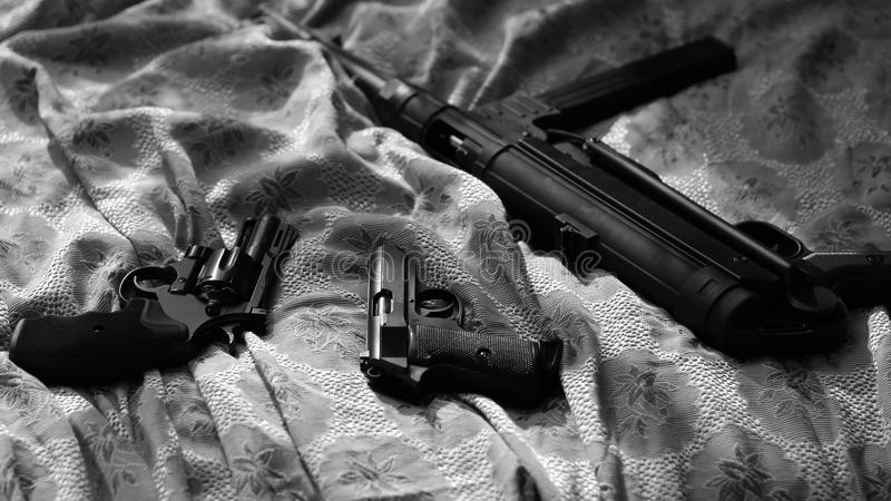 Guns On Bed Sheet. Film Noir Style. Revolver, Pistol, Machine Gun. royalty free stock photos
