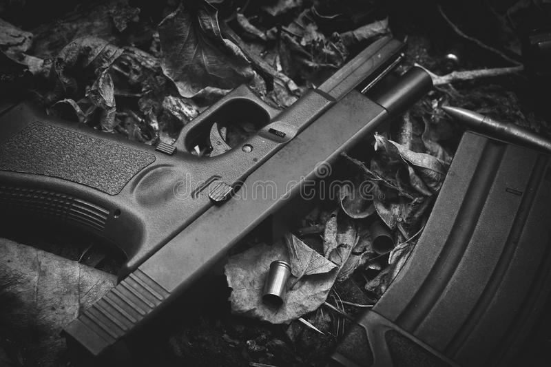Guns and bullet, Weapons and military equipment for army, 9mm pistol. Guns and bullet, Weapons and military equipment for army, 9mm pistol on dry leaves forest royalty free stock images