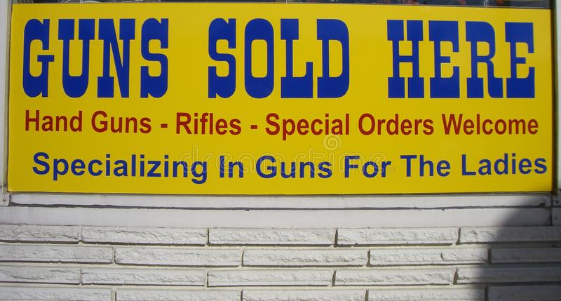 Guns sold here. Montana, USA, 2009 - Yellow shop sign saying: Guns sold here royalty free stock photography