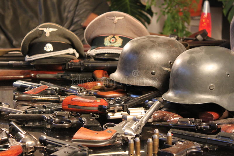 Guns and war helmets. War helmets and guns exposed on the table stock photo