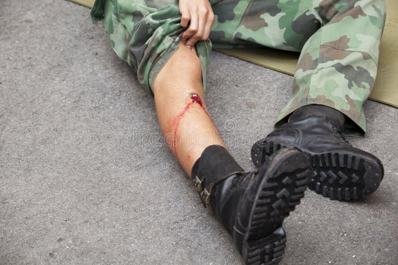 Gunshot wound on soldier's leg stock photography