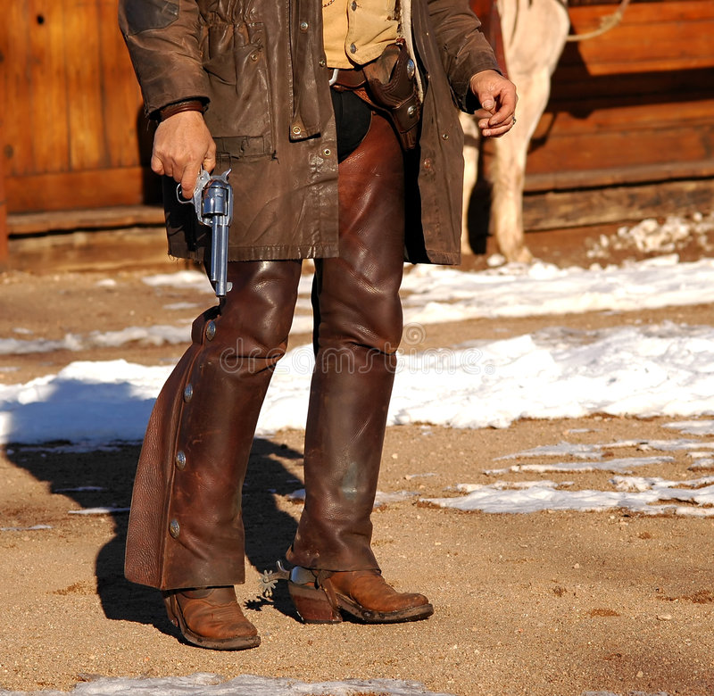 Gunslinger. Cowboy in chaps & spurs holding revolver by side stock photography