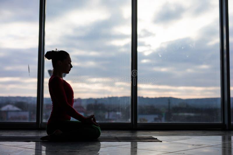 Guptasana. Beautiful yoga woman practice in a big window. Hall background. Yoga concept stock photos