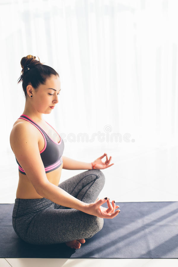 Guptasana. Beautiful yoga woman practice in a traning hall background. royalty free stock image