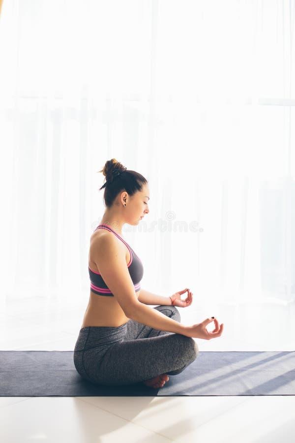 Guptasana De mooie praktijk van de yogavrouw op een achtergrond van de opleidingszaal royalty-vrije stock foto's
