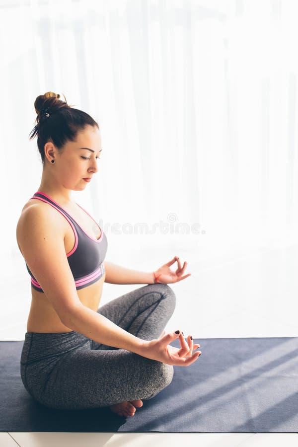 Guptasana Härlig yogakvinnaövning i en traning korridorbakgrund royaltyfri bild