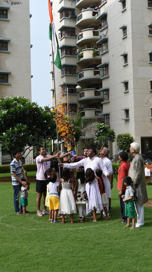 Gurgaon, Índia: 15 de agosto de 2015: Povos em uma sociedade local em Gurgaon, Deli que aumenta a bandeira no Dia da Independênci fotografia de stock royalty free