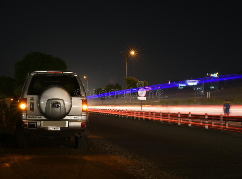 Gurgaon, India: August 19th,2015:Legendry Tata Safari SUV on an urban road in Gurgaon. With light trails of cars and bus lights with other high rise buildings stock image