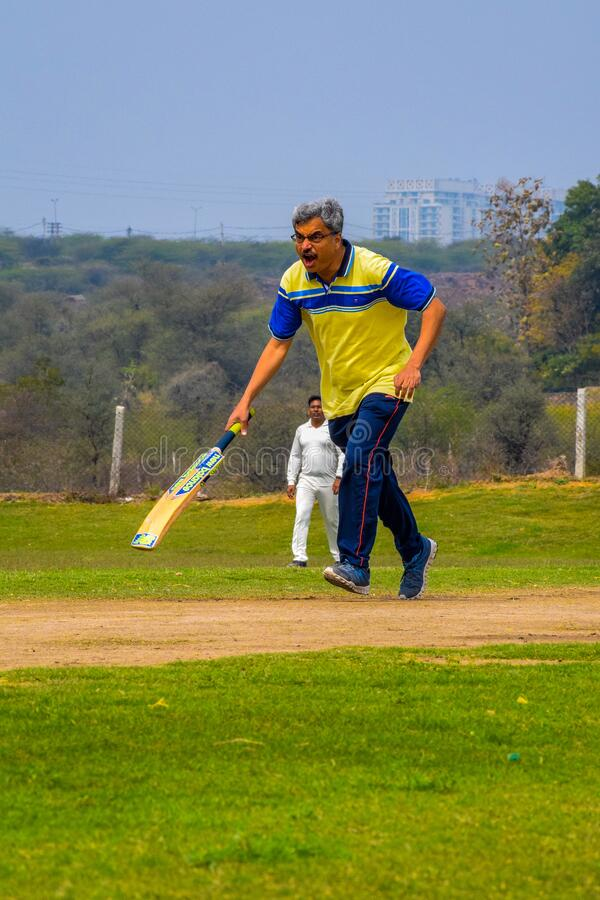 Gurgaon India – March 3 2019 : Full length of cricketer playing on field during sunny day. Gurgaon India – March 3 2019 : Full length of cricketer stock image