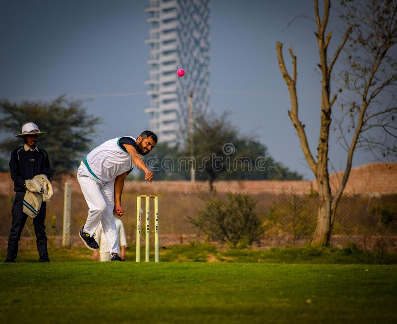 Gurgaon India – March 3 2019 : Full length of cricketer playing on field during sunny day. Gurgaon India – March 3 2019 : Full length of cricketer royalty free stock image