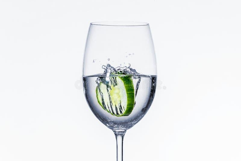 Gurkenscheibe fiel in Glas auf weißem Hintergrund stockfotos