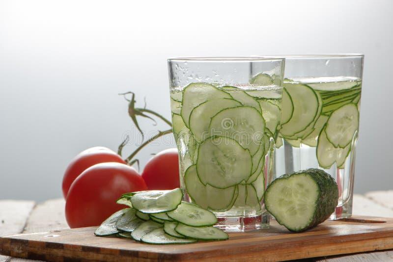 Gurkenwasser, Spülwasser, zum des Körpers zu entgiften und des Dursts auf einem weißen Hintergrund zu löschen lizenzfreie stockfotos