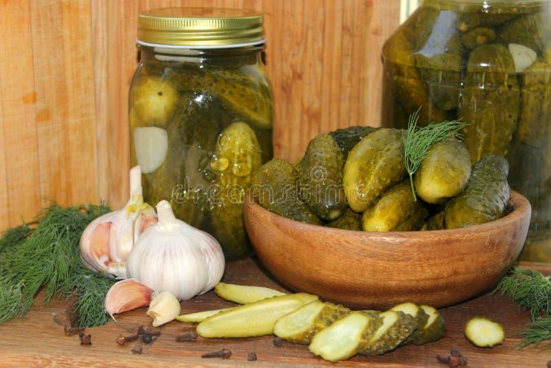 Gurkor i en träbunke, kryddor för att grava och krus av inlagda gurkor på tabellen royaltyfri bild