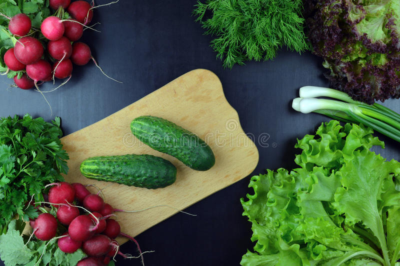 Gurkor och nya grönsaker på en skärbräda Top beskådar royaltyfria foton
