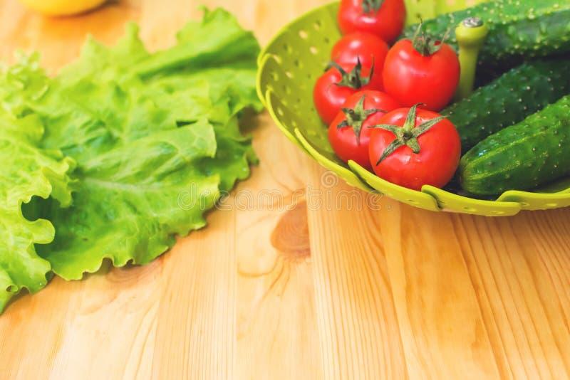 Gurkor och tomater för nya grönsaker i en grön bunke på en trätabell bredvid gröna grönsallatsidor banta vegetarian royaltyfria foton