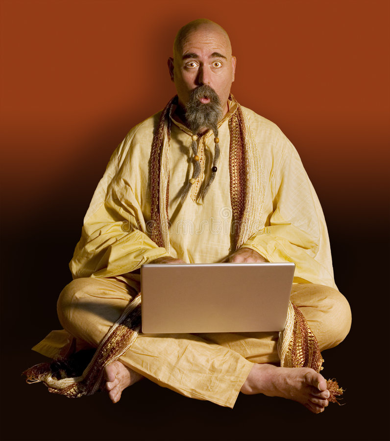 Guru wih a Laptop Computer. Guru looks surprised over the top of his laptop computer royalty free stock photo