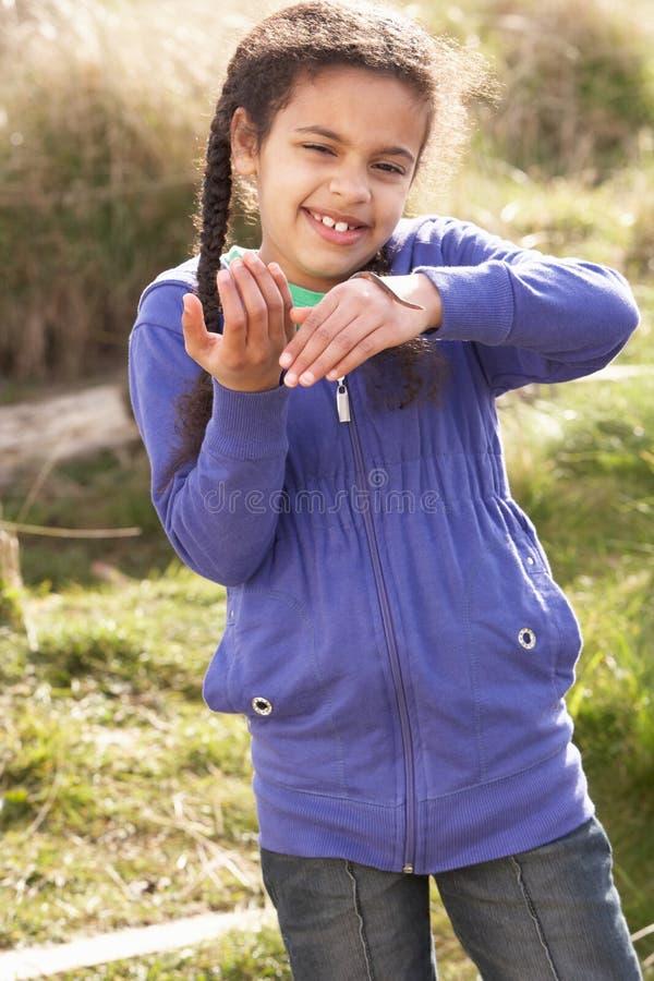 Gusano de la explotación agrícola de la chica joven al aire libre fotografía de archivo