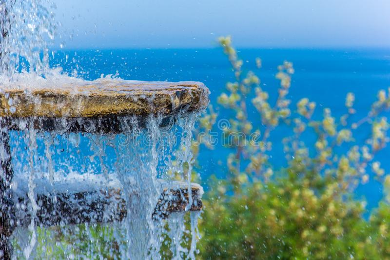The gush of water of a fountain against the blue sea royalty free stock photo