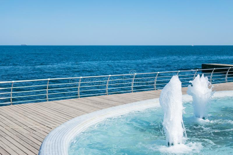 The gush of water of fountain. Splash and Foam of water. Blue vertical fountain with mosaic pool on the wooden terrace, by the se. A. Rest on the beach, sea royalty free stock photo