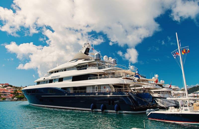 Gustavia, stbarts - 25 de enero de 2016: transporte y buque del agua Yates anclados en el embarcadero del mar en la playa tropica fotografía de archivo libre de regalías